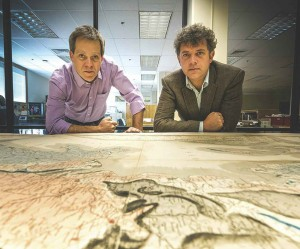 Professors Robert Gaines and Jade Star Lackey lean over the map