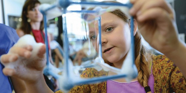 A visitor looking at a cube-type-structure with soap bubbles