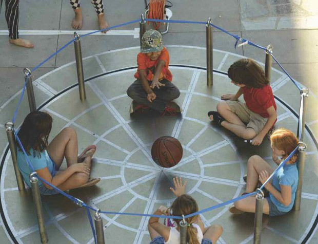 Children sitting in a circle and passing around a ball