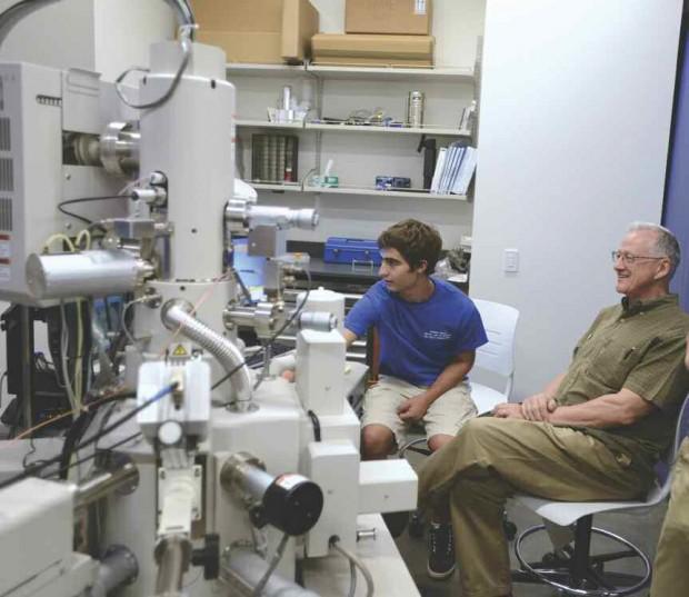 Student demonstrating microscope