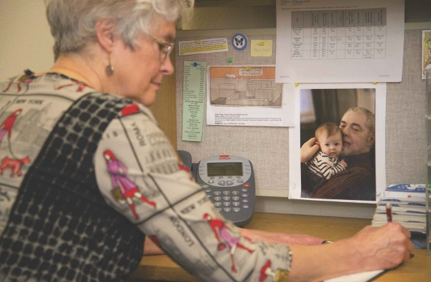 Peggy Arnold writes at her desk with a photo of Mogens Thomsen and his granddaughter