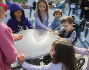 Children crowd onto the wheelchair-accessible spinning dish at the Magical Bridge playground.