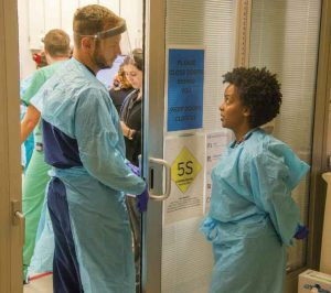 Toles and chief resident Taylor Stayton gown up for a trauma case.