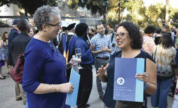 During the reception following her installation, Starr speaks with Assembly member Cristina Garcia '99.
