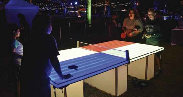 Partygoers enjoy a game of ping pong on a lighted table.