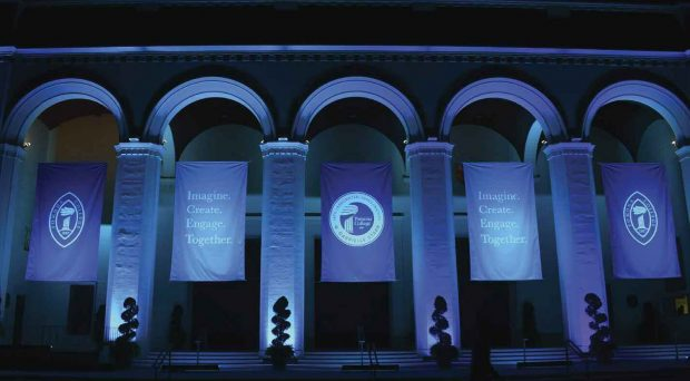 "Dramatic lighting on the front of Bridges Auditorium reveals banners with the College mark, the inaugural logo and the theme of the inauguration—""Imagine. Create. Engage. Together."""