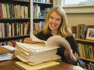 Susan McWilliams in her office with her father's manuscript and files