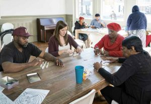Project Horseshoe Farm fellow Greta Hartmann (second from left) plays dominos with adults in the community center on Greensboro's Main Avenue