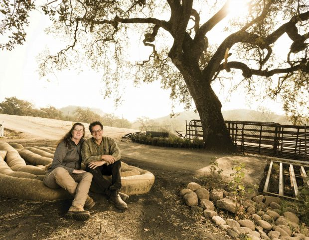 Melissa and Ken Moholt-Siebert, sit on bundles of straw beneath the eponymous ancient oak tree, which survived the 2017 fire that destroyed their home, vineyard and tasting room.