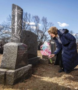 Ruth Craig '74 places flowers on the grave of Adolfo Sartini, who died of the Spanish flu in 1918.