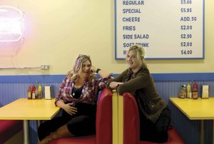 Wendy Molyneux (left) and her sister Lizzie Molyneux-Logelin chat in a working replica of the diner in Bob's Burgers.