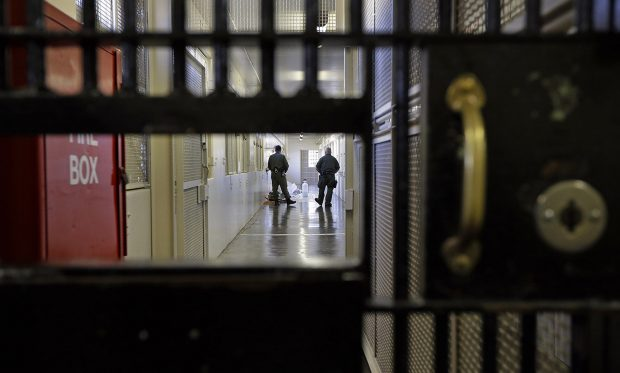 Prison guards stroll down a corridor at San Quentin State Prison in San Quentin, Calif.