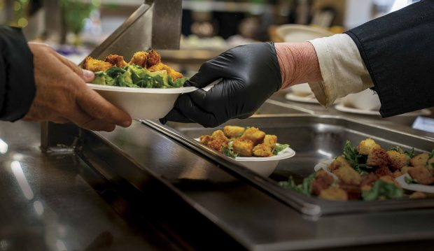 "A Dining Service employee serves a student with a salad in a ""Grab-and-Go"" container."