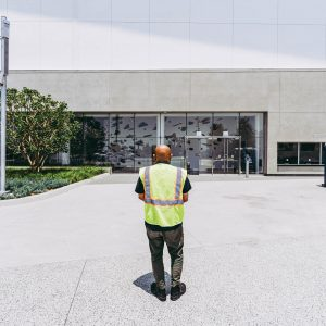 Wearing a safety vest, Professor Sandeep Murkherjee looks at his work through the entrance of the YouTube Theater at SoFi Stadium during the construction process.