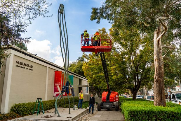 Workers survey the 30-foot sculpture ghandiG by Peter Shelton '73 at the museum's former location before moving it by crane across College Avenue to its new home.